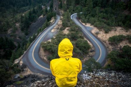 person-in-wet-weather-gear-looking-down-on-road
